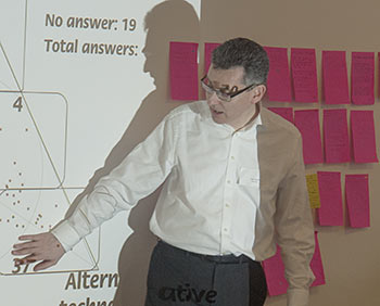 Tony Quinlan explaining how to interpret SenseMaker signifiers. The pink objects behind him are the micro-narratives we produced during the exercise, on 'super-sticky' Post-It notes. Photo Conrad Taylor.